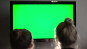 Two young long haired blond watching green TV screen and laughing. Two young long-haired blond watching green TV screen and laughing stock footage
