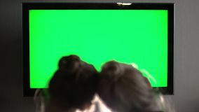 Two young long haired blond watching green TV screen and straighten head stock footage