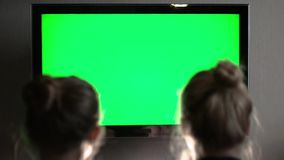 Two young long-haired blond watching green TV screen and suddenly turn their heads together. HD stock video footage