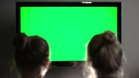 Two young long-haired blond watching green TV screen and tilt their heads to one another. HD stock footage