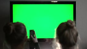 Two young long haired blond watching green TV screen and use remote control stock video