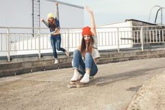Two young  longboarding girl friends Stock Photo