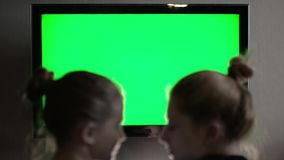Two young longhaired blond watching green TV screen and suddenly turn their heads together stock footage