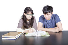 Two young lover students studying, isolated. Royalty Free Stock Photography