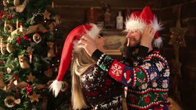 Two young lovers in funny sweaters wearing santa`s hut to each other and kissing.  stock video footage