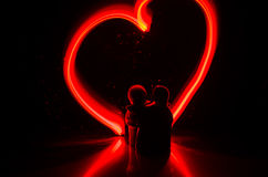 Two young lovers paint a heart on fire. Silhouette of couple and Love words on a dark background Stock Photos