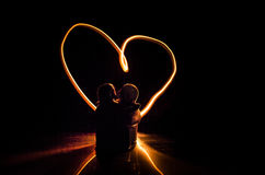 Two young lovers paint a heart on fire. Silhouette of couple and Love words on a dark background Royalty Free Stock Photo