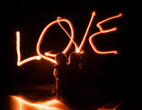 Two young lovers paint a heart on fire. Silhouette of couple and Love words on a dark background Stock Images