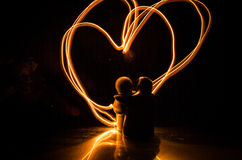Two young lovers paint a heart on fire. Silhouette of couple and Love words on a dark background Royalty Free Stock Photography