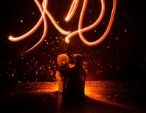 Two young lovers paint a heart on fire. Silhouette of couple and Love words on a dark background Royalty Free Stock Photos