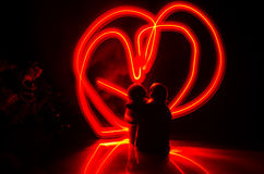 Two young lovers paint a heart on fire. Silhouette of couple and Love words on a dark background Stock Image