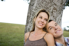 Two young lovers sitting beneath a tree Royalty Free Stock Images