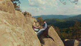 Two young lovers are sitting on the top of a rock in the mountains and holding their hands. Couple goals. Being happy. Together. Extreme relationships stock video footage