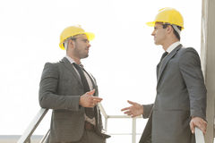 Two young male architect discussing on stairway Royalty Free Stock Images