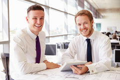 Two young male architects working together, look to camera Royalty Free Stock Photos