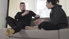Two young male Caucasian friends eating pizza and talking. Adult university students resting indoors on weekends