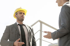 Two young male engineers discussing on stairway against clear sky Royalty Free Stock Photo