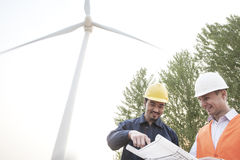 Two young male engineers in hardhats looking down at a blueprint in front of a wind turbine Stock Images
