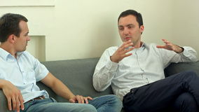 Two young male friend sitting on sofa and chatting at room. Men talk concept. Professional shot on BMCC RAW with high dynamic range. You can use it e.g in your stock video footage