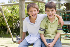 Two young male friends at a playground smiling Stock Photo