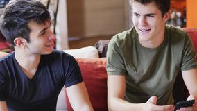 Two young men talking and chatting. Two young male friends talking and chatting while sitting on sofa at home, relaxing and having fun together stock image