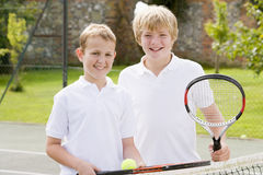 Two young male friends on tennis court. Two young male friends with rackets on tennis court smiling stock photography