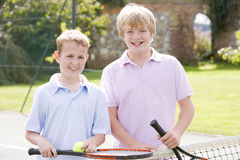 Two young male friends on tennis court smiling. Two young male friends with rackets on tennis court smiling stock photos