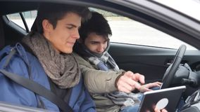 Two young male friends using tablet computer in car. Two casual young men friends sitting in a car, sharing information and using tablet computer stock video