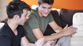 Two young male friends using tablet computer. Two casual young men friends relaxing on sofa at home sharing information and using tablet computer stock footage