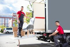 Male Movers Loading Cardboard Boxes In Truck On Street
