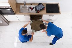 Two Movers Placing Dishwasher In Kitchen. Two Young Male Movers In Uniform Placing Dishwasher In Kitchen royalty free stock photo