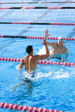 Two young male swimmers giving high-fives in swimming pool stock image