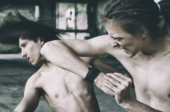 Two young man bare knuckle fighting in abandoned building Stock Image