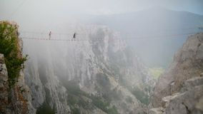 Two young guy crosses abyss on rope bridge, experiencing adrenaline stock video footage