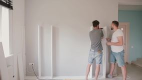 Two young man do the repairing in the bright living room. Men assemble white furniture together. Two young man friends do the repairing in the bright living stock video footage