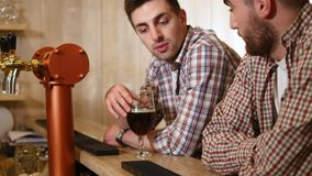 Two young man drinks beer behind a bar counter. Selective Focus stock video footage