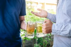 Two young man hand raise a glass of beer to celebrate the holiday festival happy drinking beer outdoors and enjoying at home royalty free stock photo