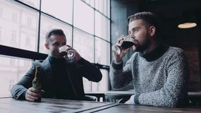 Two young man having mug of lager beer in a deserted pub, they toast and praise the taste. Little party, alcoholic stock footage