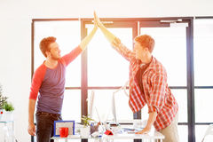 Two young man in office clapping their hands Stock Image
