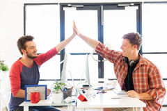 Two young man in office clapping their hands Stock Photo