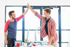 Two young man in office clapping their hands Stock Photos