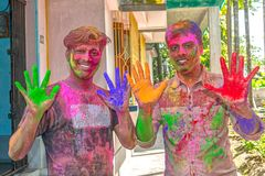 Two young man showing colorful painted hands during Holi festival in India stock images