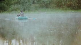 Two young man sitting in the rubber boat and rowing with paddles in the morning. Two male on the lake with fog on it. stock video