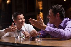 Two young man talking at counter. Stock Images