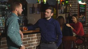 Two young man talking at counter. two friends standing in bar and drinking whisky. Two young man talking at counter. two friends standng in bar and drinking stock video