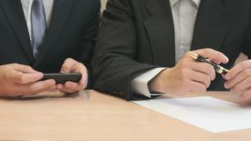 Two young man at the university. Two young unknown students in formal suits sitting at the wooden desk at university in the classroom look for something in the stock video footage
