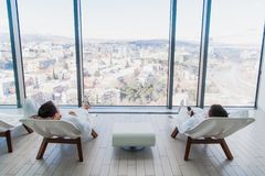 Two young man wearing bathrobe, lying on lounger in spa salon and talking to each other in front of a big window with a royalty free stock photo