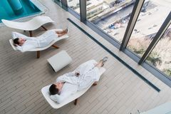 Two young man wearing bathrobe, lying on lounger in spa salon and talking to each other in front of a big window with a stock photo