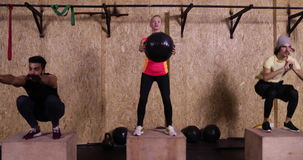 Two Young Man And Woman In Gym Sport Exercising, Girl Squating With Ball Crossfit Training, Sportsman Group Working Out stock footage
