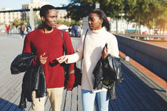 Two young man and woman students walking on a campus during break between lectures in University, Royalty Free Stock Photography